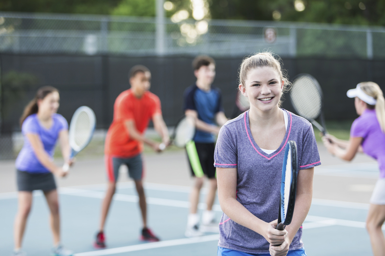 Multi-ethnic group of teenagers (14 to 16 years) at tennis clinic with instructor (30s).  Focus on girl in foreground (15 years).