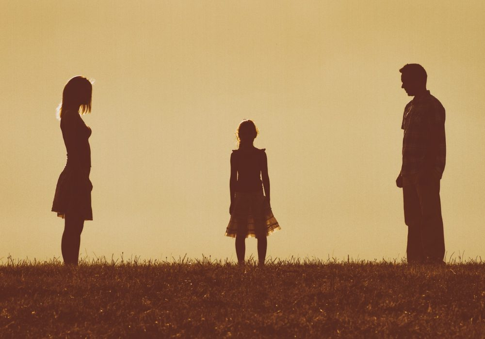 Silhouette of a angry husband and wife  on each other looking at their daughter and waiting for her to choose between them.Image is intentionally with grain and toned.